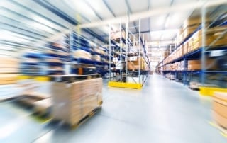 Warehouse building at floor level showing shelves of goods with speed blur effect