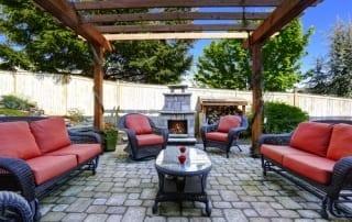 Backyard modern patio area with wicker furniture set and brick fireplace