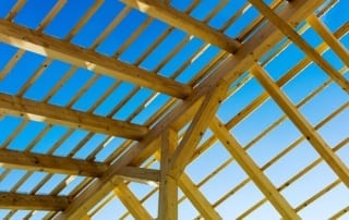 New wooden roof frame viewed from below with blue sky