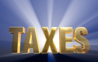 """Gold capital letter word """"TAXES"""" on a dark blue background brilliantly backlit with light rays shining through from the light source."""