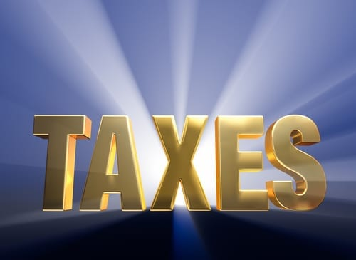 "Gold capital letter word ""TAXES"" on a dark blue background brilliantly backlit with light rays shining through from the light source."
