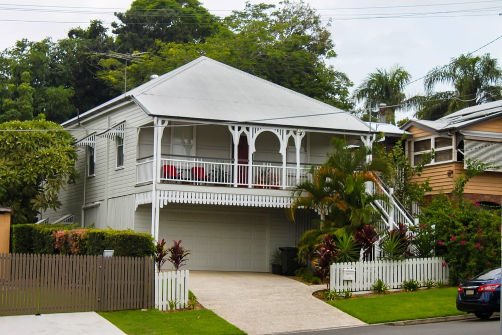 White queenslander home with tropical greenery