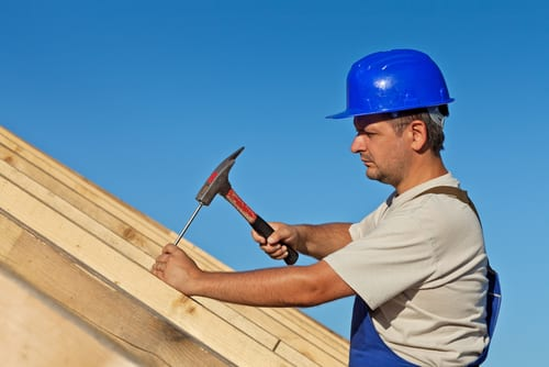 Carpenter working on the roof - driving in big nail