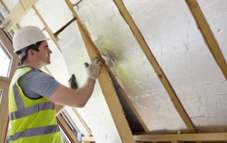 Builder Installing Insulating Board Into Roof Of House